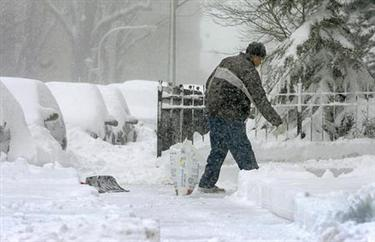 Harold Coleman spreads salt to help melt snow on the sidewalk he just shoveled outside the sandwich shop where he works Saturday, Jan. 22, 2005 in Chicago. Heavy snow pounded the Chicago area overnight and continued into Saturday. (AP Photo/Jeff Roberson)