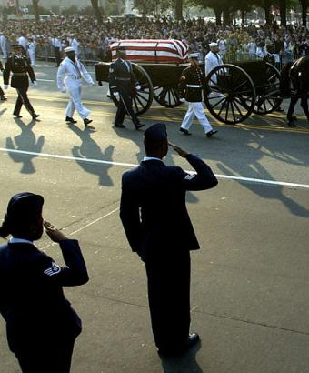Members of the U.S. Air Force salute as former President Ronald Reagan's casket is carried on a horse-drawn caisson enroute to the U.S. Capitol in Washington, D.C., Wednesday, June 9, 2004. (AP Photo/Eric Gay)