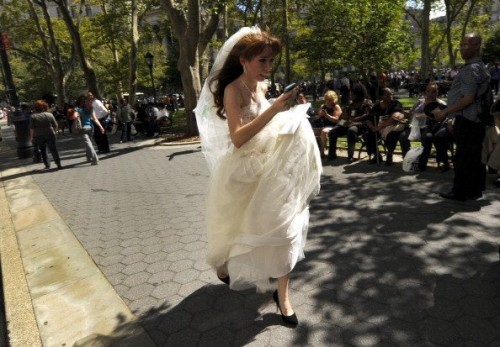 "Valeriya Shevchenko, 18, evacuated a NY courthouse during the earthquake panic but the eye-catching photo of her wedding-dress dash created complications. The young bride and groom were keeping the nuptials a secret from their disapproving families -- not such an easy feat with the highly circulated image that is now being called the ""Earthquake Bride."" ""They'd say we're too young and not for each other. His mom is going to go crazy,"" Shevchenko told the New York Post. The couple married later that day. (Photo: TIMOTHY A. CLARY/AFP/Getty Images)"