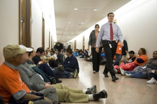Protesters from the Occupy Wall Street movement fill the hallway outside of the offices of U.S. Senator Scott Brown (R-MA) (not pictured) on Capitol Hill in Washington December 6, 2011. REUTERS/Jonathan Ernst (UNITED STATES - Tags: POLITICS CIVIL UNREST)