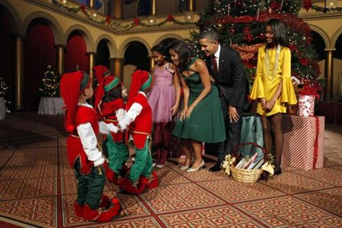 President Barack Obama and first lady Michelle Obama with Malia, right, and Sasha, left, greet children dressed like elves at the annual Christmas in Washington taping at the National Building Museum in Washington, Sunday, Dec. 11, 2011. Host Conan O'Brien, Justin Bieber, Cee Lo Green, Jennifer Hudson, Victoria Justice and The Band Perry were to perform. (AP Photo/Jacquelyn Martin)