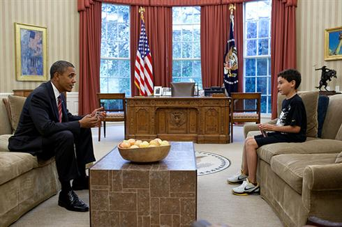 """Nicky DeParle, son of Deputy Chief of Staff Nancy-Ann DeParle, was in the White House to visit his mother one afternoon on a school holiday. The President took a break between meetings to have a power bar with Nicky and check on how he was doing.""  (Official White House Photo by Pete Souza)"