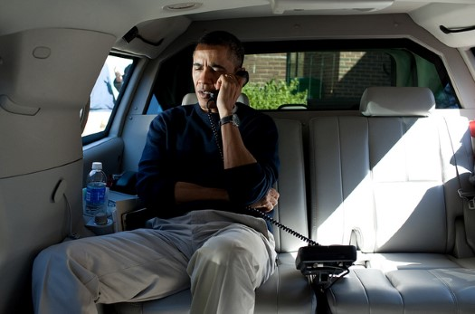 President Barack Obama talks on the phone with Afghanistan President Hamid Karzai from his vehicle outside the Jane E. Lawton Community Center in Chevy Chase, Maryland, Sunday, March 11, 2012. The President called to express his shock and sadness over the reported killing of Afghan civilians. (Official White House Photo by Pete Souza)