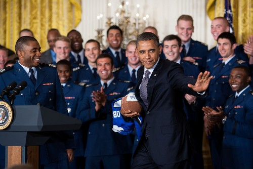 President Barack Obama strikes the Heisman pose after accepting a football from quarterback Tim Jefferson, left, during the Commander-in-Chief Trophy presentation to the United States Air Force Academy football team in the East Room of the White House, April 23, 2012. The Air Force beat Army and Navy in 2011 to claim the trophy for the 18th time. (Official White House Photo by Pete Souza)