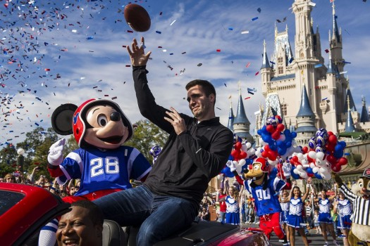 Baltimore Ravens quarterback and Super Bowl XLVII Most Valuable Player Joe Flacco rides with Mickey Mouse in a parade through the Magic Kingdom at Walt Disney World Resort in Lake Buena Vista, Florida rides in this handout provided by Walt Disney World Company February, 4, 2013. REUTERS/Matt Stroshane/Walt Disney World/Handout