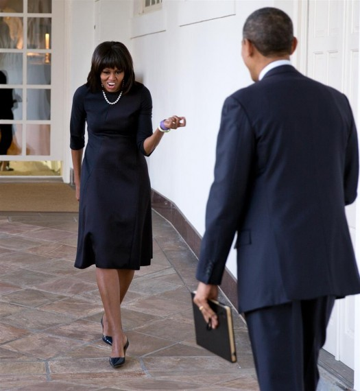 President Barack Obama watches as First Lady Michelle Obama playfully greets him on the Colonnade of the White House, Feb. 12, 2013.