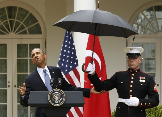 U.S. President Barack Obama checks to see if he still needs the umbrella held by a U.S. Marine to protect him from the rain during a joint news conference with Turkish Prime Minister Recep Tayyip Erdogan in the Rose Garden of the White House in Washington, May 16, 2013. REUTERS/Jason Reed (UNITED STATES - Tags: POLITICS TPX IMAGES OF THE DAY)