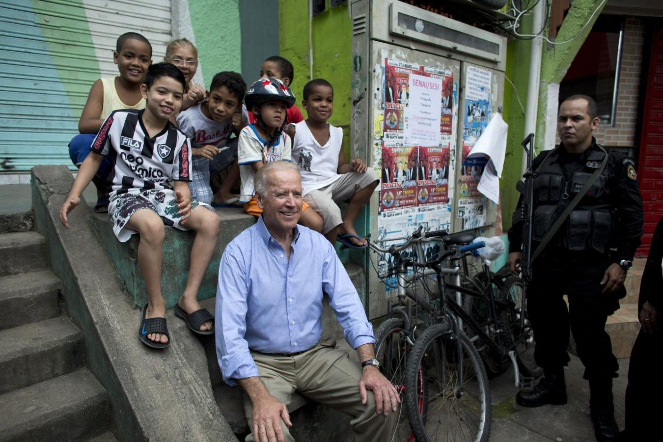 U.S. Vice President Joe Biden poses for photos with children as he tours the Santa Marta slum, as a special force police officer stands by in Rio de Janeiro, Brazil, Thursday, May 30, 2013. Biden met residents of the hillside slum in Rio's south zone during a 30-minute visit. (AP Photo/Victor R. Caivano