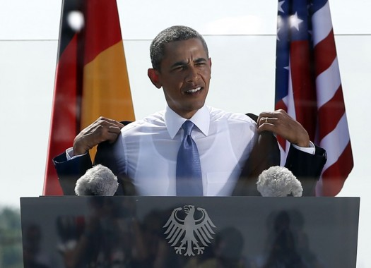 US President Barack Obama takes off his jacket due to warm weather while he delivers a speech in front of Brandenburg Gate in Berlin Wednesday, June 19, 2013. On the second day of his visit to Germany, Obama met with German President Joachim Gauck and Chancellor Angela Merkel before delivering a speech at Brandenburg Gate. (AP Photo/Michael Sohn)