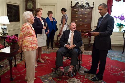 Former President George H. W. Bush and former First Lady Barbara Bush present President Barack Obama with a pair of socks in the Map Room of the White House, July 15, 2013. (Official White House Photo by Pete Souza)