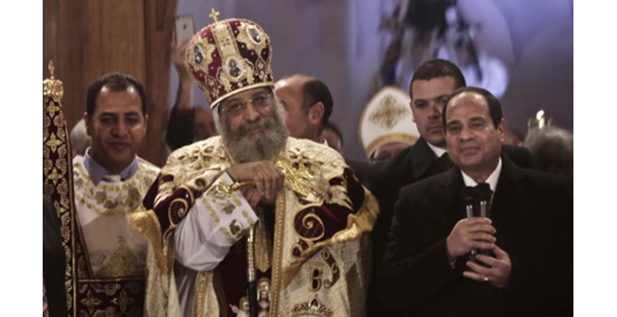 Egypt's President Abdel-Fattah El-Sisi, right, visits Coptic Pope Tawadros II, center, during Christmas Eve Mass at St. Mark's Cathedral, in Cairo, Egypt, Tuesday, Jan. 6, 2015 (Photo: AP)