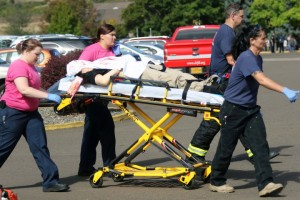 Authorities carry a shooting victim away from the scene ... (Mike Sullivan/Roseburg News-Review via AP)
