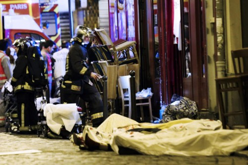 A rescue worker walks plast a victim in the 10th district of Paris, Friday, Nov. 13, 2015.  At least 35 people were killed Friday in shootings and explosions around Paris, many of them in a popular concert hall where patrons were taken hostage, police and medical officials said. (AP Photo/Jacques Brinon)