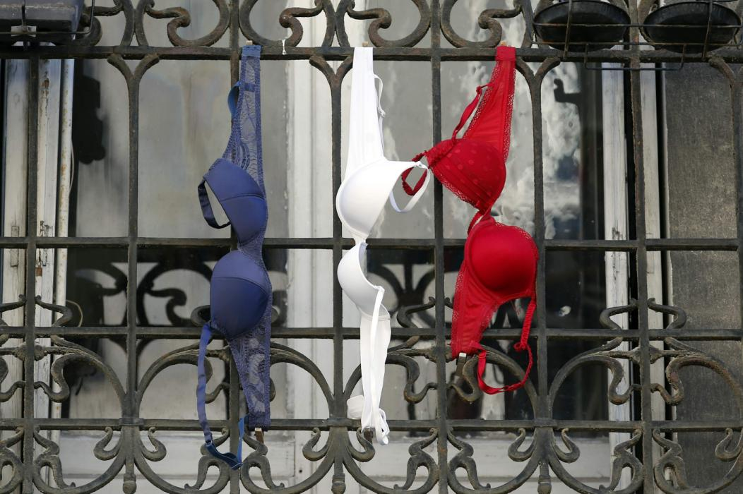 Blue, white and red brassieres, the colours of the French national flag, hang from a balcony in Marseille, France, November 27, 2015 as the French President called on all French citizens to hang the tricolour national flag from their windows on Friday to pay tribute to the victims of the Paris attacks during a national day of homage. (REUTERS/Jean-Paul Pelissier)